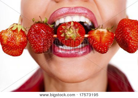 Woman`s mouth  with red strawberries stickied on skewer isolated on white background