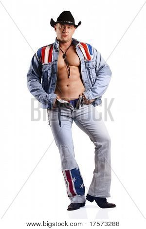 A muscular man in a cowboy hat  lets down blue jeans. Isolated on white.
