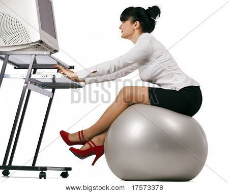 Smiling business woman doing exercise with a grey workout ball working on a computer, over white background