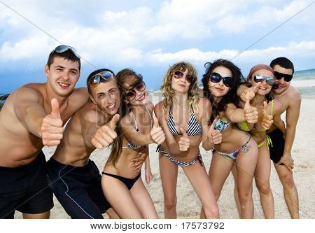 Freudige Team von Freunden, die Spaß am Strand und zeigt Ordnung Zeichen