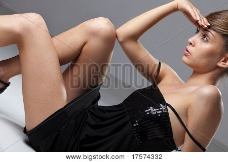 Portrait of an elegantly beautiful young woman in black dress posing on the dark floor