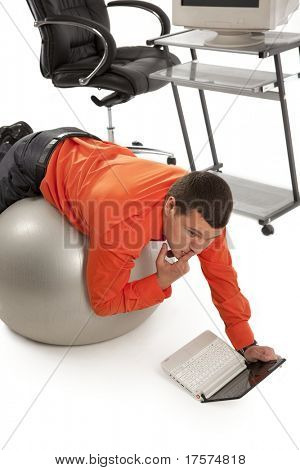 Young businessman doing gim with grey ball, looking on laptop screen.