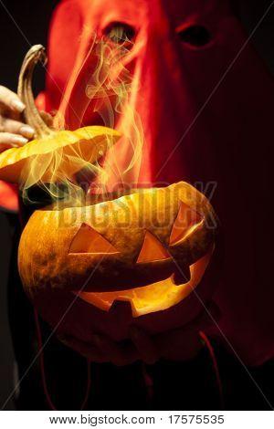 Executioner holding halloween fumy pumpkin