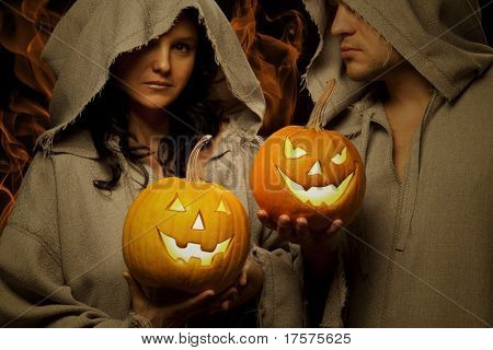 Mystic shoot - A couple, dressed in a robe of monks holding halloween glowing pumpkins
