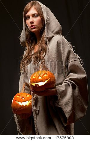 woman in robe holding halloween pumpkins
