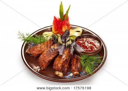 Plate with pork ribs with vegetables and chili sauce isolated on white background