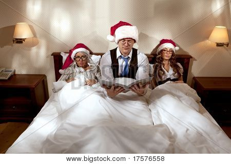Manager with two his subordinates reading a business plan sitting in bed on New Year's night
