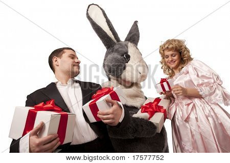 Portrait of big grey fur's color rabbit giving present to a pretty girl in pink dress and Gentleman with gift boxes. Isolated over white background