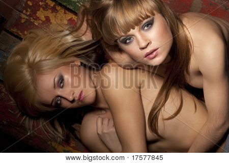 Nude portrait of two sexy girls posing on dark background