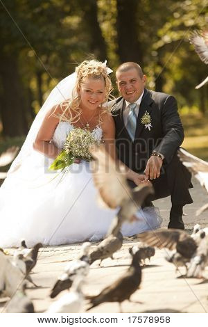 Beautiful bride and groom feeding doves