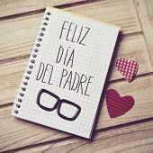 the text feliz dia del padre, happy fathers day in spanish written in the page of a notebook, a pair poster