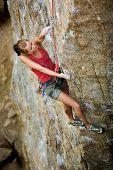 Постер, плакат: Женский рок альпинист достигая для следующего места