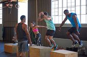 Crossfit class jumping on wooden boxes guided by trainer, strength training fitness workout in gym poster