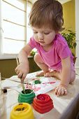 Beautiful baby girl sitting on the table covered in bright paint and painting with finger paints and