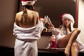 picture of promiscuous  - Portrait of two sexy girls in Santa hats with the glasses of champagne waiting for New Year - JPG