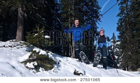 Two acive seniors in an alpine setting enjoying the sun. They wear snowhoes and have ski poles.