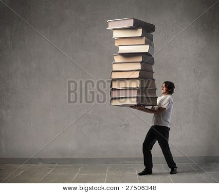 Man carrying a stack of books