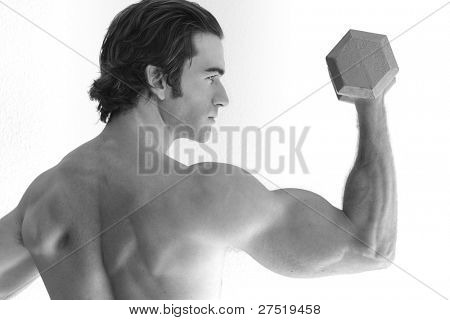 young man lifting weights in black and white