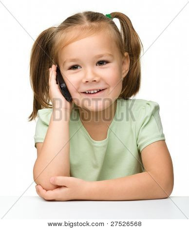 Menina bonitinha está falando no telefone celular enquanto está sentado na mesa, isolada sobre o branco