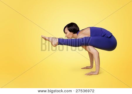 woman doing yoga arm balance and smile