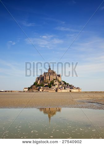 the famous Mont-St-michel on a summer morning at ebb tide, partially reflected in the water