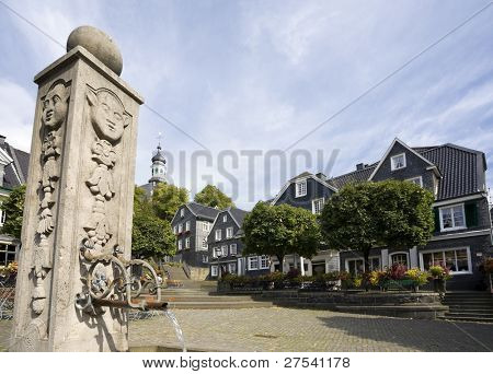 marketplace and fountain at Solingen Graefrath, surrounded by slate covered houses that are typical for the region Bergisches Land