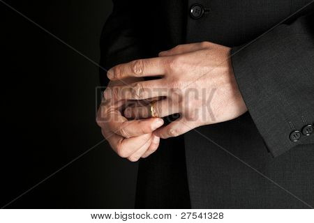 mature man taking off his golden wedding ring, close-up on hands
