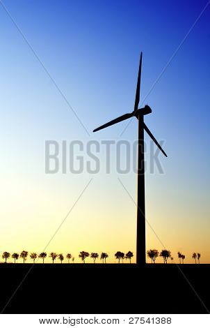 wind turbine at dawn, trees in background