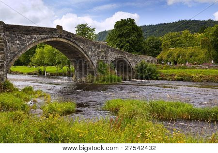 Medieval stone bridge across the river Conwy and old cottage covered with vine leaves, Llanwrst, North Wales