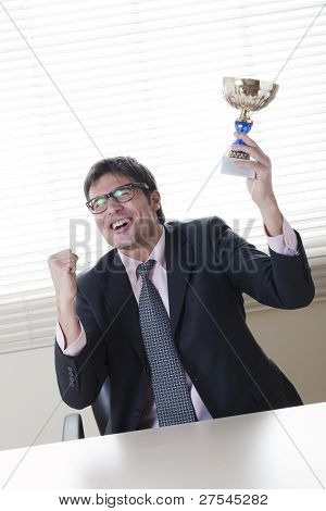 Businessman celebrating raising a cup. Concept: winning the challenge/emerging