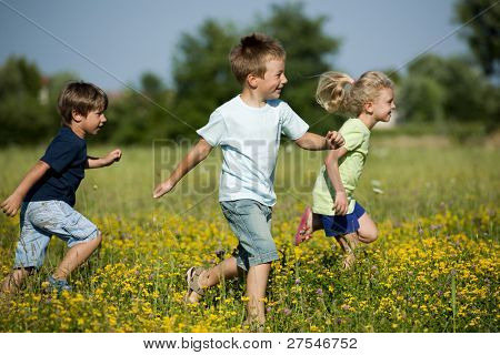 Three cute children running outdoors