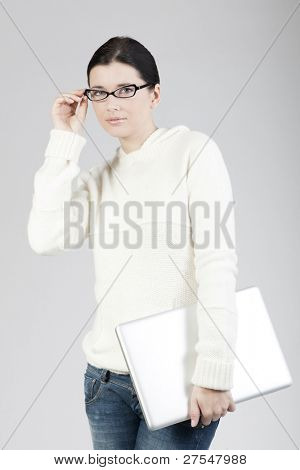 Portrait of a young woman holding a laptop computer, businesswoman or student