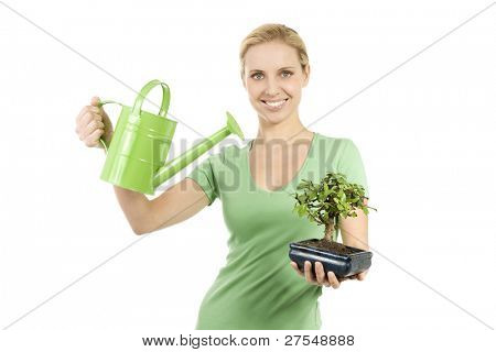 Young woman watering a bonsai tree; concepts: giving life, the beginning