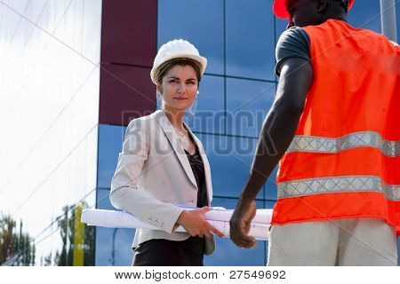 Young female engineer discussing a building project with a construction worker