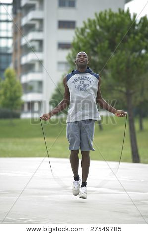 Young man jumping rope outdoors