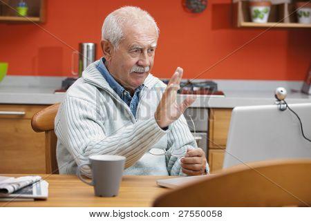 Senior man speaking through webcam in his kitchen