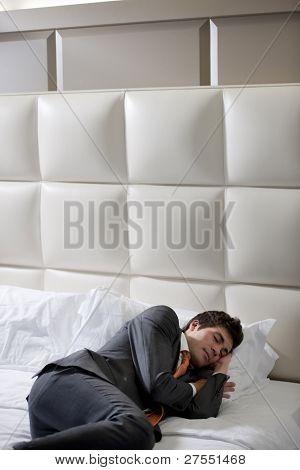 Businessman Asleep In Hotel Bedroom