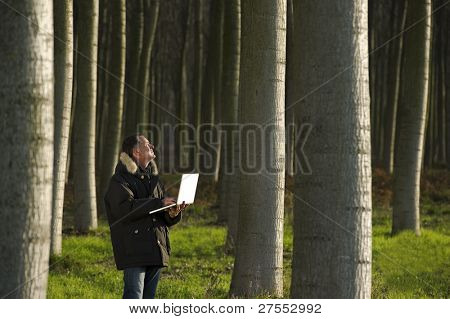 Botanist working with laptop inside a poplar wood
