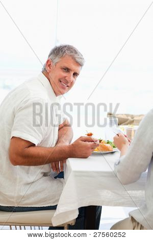 Side view of smiling mature man having dinner
