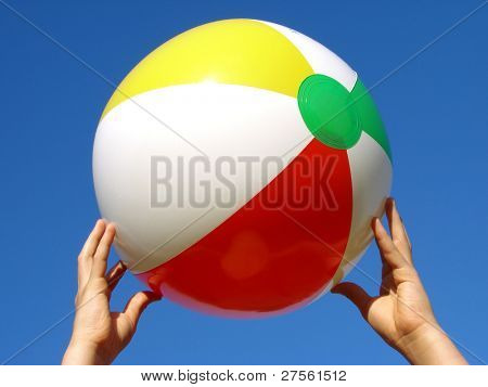 child hands with beach ball against blue sky
