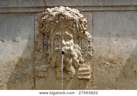 Funny mascaron face on fountain in Alhambra Granada Spain