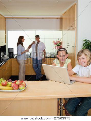 Geschwister mit ihrem Laptop in der Küche mit Eltern dahinter