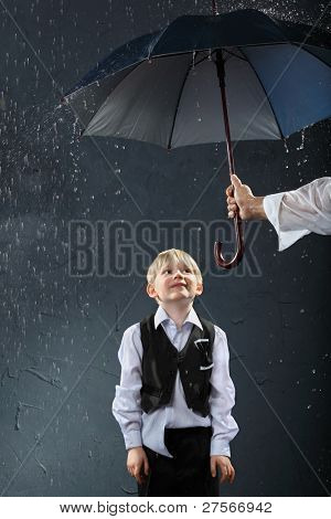 smiling boy dressed in white shirt and black vest standing under umbrella in rain; man hand holds umbrella
