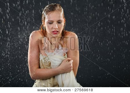 beautiful girl wearing in dress with corset freezes in rain and tries to keep warm