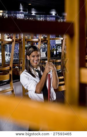 Pretty worker with a broom in a closed bar