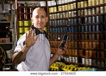 Man standing in front of colored inks in print shop