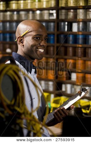 Young African American male worker working in print shop by shelves of ink