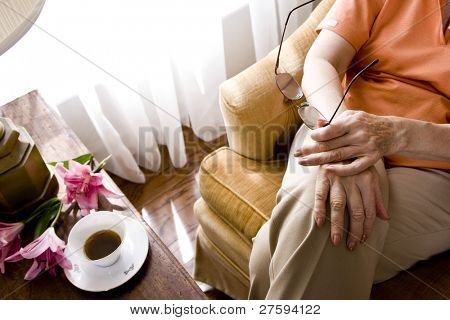 Cropped view of elderly woman sitting on armchair