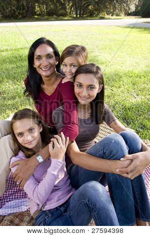 Indian mother and three children enjoying family picnic in park on sunny day