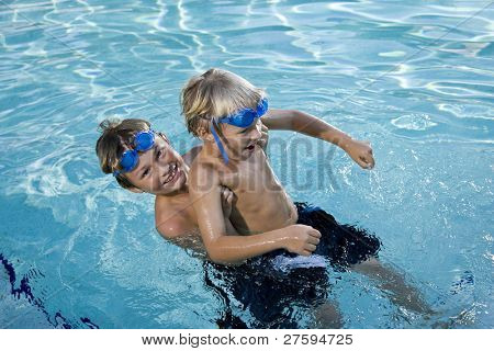 Boys will be boys - playing on side of swimming pool, 7 and 9 years
